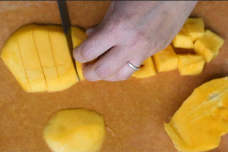 Peeled mango on cutting board by Plantainsandchallah.com
